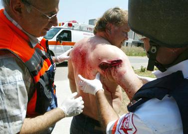 פרמדיקים בוחנים פצוע מקטיושה שנורתה על ידי החיזבאללה על כפר גלעדי, 6 לאוגוסט 2006 (צילום: פלאש 90)