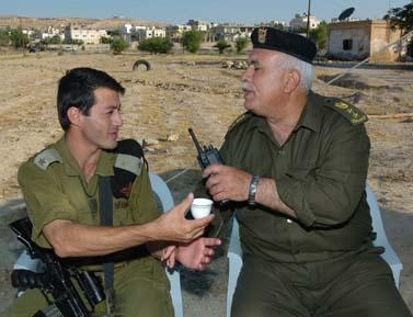 קצין פלשתיני וישראלי שותים קפה בכניסה ליריחו, 26 למאי 2006 (צילום: נתי שוחט)
