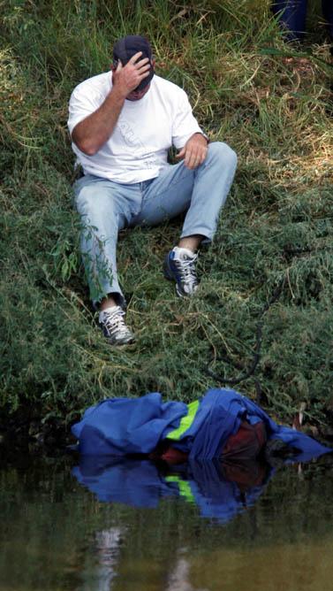 שוטר ליד המזוודה שבה נמצאה גופתה של הילדה רוז פיזם. גדות הירקון, 11 בספטמבר 2008 (צילום: רוני שוצר)