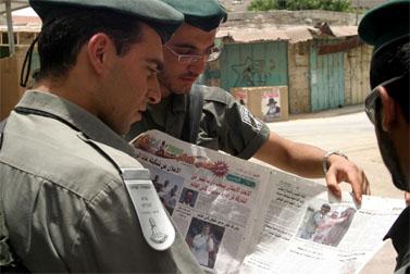 """שוטרי מג""""ב מעיינים בעיתון """"אל קודס"""". חברון, מאי 2006 (צילום: פלאש 90)"""