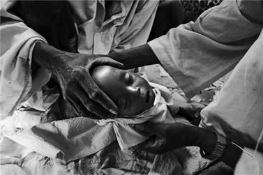 מכינים לקבורה את גופתו של חאפיז מאליק יאיא, בן תשעה חודשים, שנפטר מתת-תזונה. צ'אד, 5.6.04 (צילום: ברונו סטיבנס)