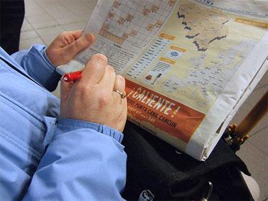 """אדם פותר תשבץ בעיתון """"מטרו"""" בתחנת רכבת בבריסל (צילום: Squonk, רישיון cc)"""