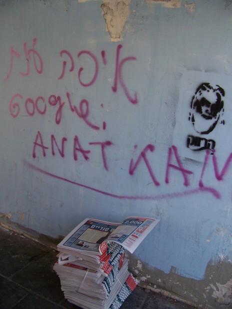 """גליונות """"ישראל היום"""" מה-9.4, למחרת הסרת צו איסור הפרסום על הפרשה, מונחים ליד קיר מעוטר בכתובת גרפיטי בתל אביב. צילום: עידו קינן, """"העין השביעית"""" (cc-by-nc-sa)"""