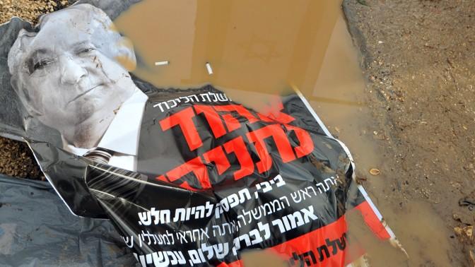 כרזה ועליה פוטו-מונטאז' של בנימין נתניהו ואהוד ברק, מושלכת בבוץ ליד התחנה המרכזית בירושלים, אתמול (צילום: יואב ארי דודקביץ')