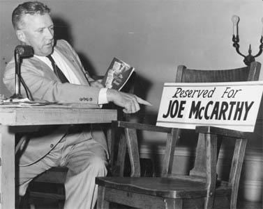 המועמד הרפובליקאי העצמאי לסנאט ליאונרד שמידט מצביע על העדות המוחשית להעדרו של יריבו, ג'וזף מקארתי, מהעימות הציבורי שהיה אמור להיערך ביניהם. 3.8.1952 (צילום: ויסקונסין היסטוריקל אימאז'ס, רשיון cc-by-nc-nd)