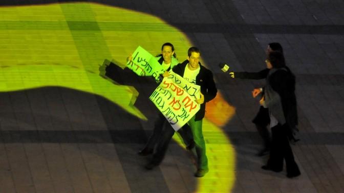 יואל שליט ובת זוגו יערה וינקלר מניפים שלטי מחאה באמצע טקס הדלקת המשואות (צילום: יואב ארי דודקביץ')