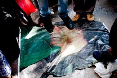 מפגינים רומסים את דיוקן קדאפי (צילום: Maggie Osama, רישיון CC BY-NC-SA 2.0)