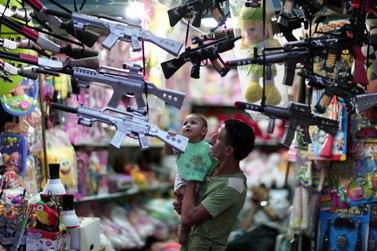 אב ובנו בוחנים צעצועים לקראת עיד אל-פיטר, השבוע בעזה (צילום: ויסאם נסאר)