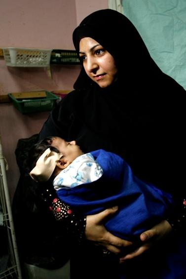 """פלסטינית מחזיקה את בנה, שנפצע מירי צה""""ל (צילום: עבד רחים חטיב)"""