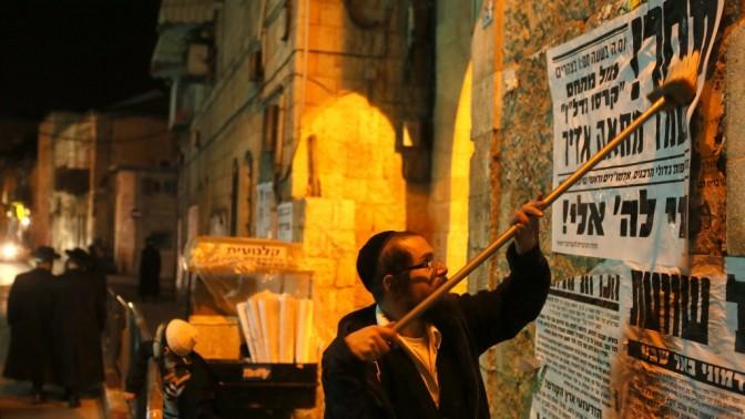 חרדי מדביק פשקווילים על קירות מאה-שערים בירושלים (צילום: נתי שוחט)