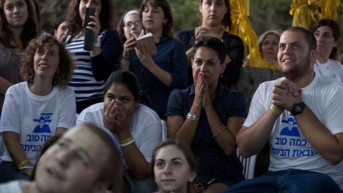 """ישראלים צופים בטלוויזיה בשובו של החייל גלעד שליט משבי חמאס. אוהל המחאה של """"מטה המאבק למען שליט"""", מול בית ראש הממשלה בירושלים. 18.11.11 (צילום: דוד ועקנין)"""