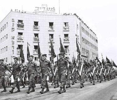 """מצעד צבאי על רקע בית """"מעריב"""" בתל-אביב. יום העצמאות, 9.5.1962 (צילום: פריץ כהן, לע""""מ)"""
