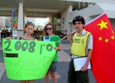 מפגינים מטעם אמנסטי בפתח המלון שבו נערכה מסיבת העיתונאים