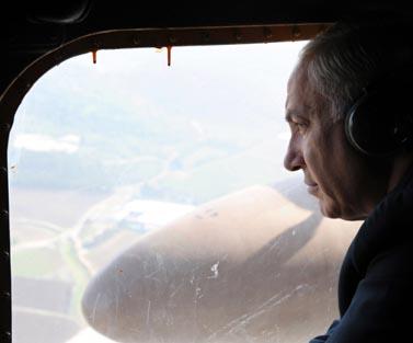"""ראש הממשלה בנימין נתניהו במסוק בדרכו לטקס הזיכרון להרוגי השריפה בכרמל, שלשום (צילום: משה מילנר, לע""""מ)"""