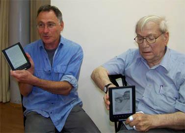 הסופרים יורם קניוק (מימין) ואיל מגד, אוחזים במכשירי עברית (צילום: עידו קינן, חדר 404, cc-by-sa)