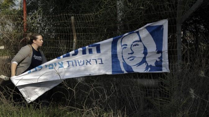 פעילה של מפלגת התנועה של ציפי לבני מסירה כרזה בתום עצרת בחירות באשקלון, אתמול (צילום: צפריר אביוב)