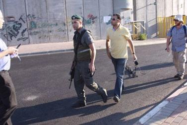 """מלמעלה: כתב ערוץ 7 חזקי עזרא ושוטר המג""""ב שלטענתו שבר את מצלמתו; הכתב נעצר באשמת תקיפת שוטר . צילום: עמנואל מימון"""