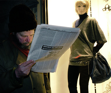 אדם קורא עיתון ליד חלון ראווה במולדובה (צילום: דורין ניקולסקו-מוסטטה, רשיון cc-by-nc-nd)