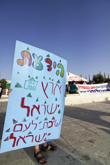 שלט שנישא במאהל שהוקם מול בית-המשפט העליון בירושלים, במחאה על הכוונה להריסת שכונה בבית-אל. אתמול (צילום: ליאור מזרחי)