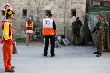עובד הסהר-האדום עומד בין ליצנים פלסטינים לחיילים ישראלים, אתמול בחברון (צילום: מתניה טאוסיג)