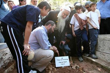 אביו ואחיו של אברהם דוד מוזס, ליד קברו הטרי בגוש עציון (צילום: פלאש 90)