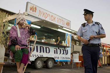 שוטר מביט במופע רחוב בירושלים (צילום: מתניה טאוסיג / פלאש 90)