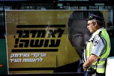 שוטר וכרזת בחירות, היום בירושלים (צילום: אוליביה פיטוסי)