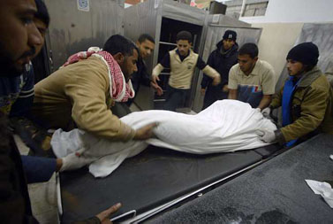 """פלשתינים אוספים את גופתו של מחבל שחוסל בתקיפה אווירית של צה""""ל, אתמול ברפיח (צילום: עבד רחים כתיב)"""