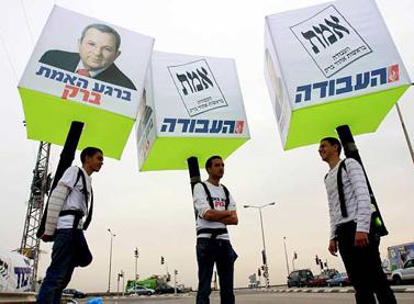 נושאים על גבם שלטי בחירות, אתמול ליד אשקלון (צילום: אדי ישראל)