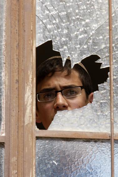 נער מביט מחלון בישיבת מרכז-הרב על הלווית הנערים שנרצחו בפיגוע בישיבה אתמול (צילום: פלאש 90)