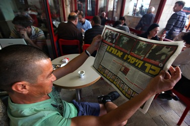 אדם מעיין בעיתון, אתמול (צילום: קובי גדעון)