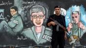 שוטר חמאס על רקע ציורי קיר של גלעד שליט (צילום: ויסאם נסאר)