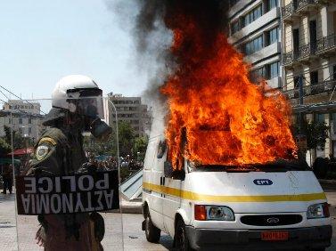 שוטר לצד ניידת שידור עולה באש, יוון (צילום: PIAZZA del POPOLO, רשיון CC BY 2.0)