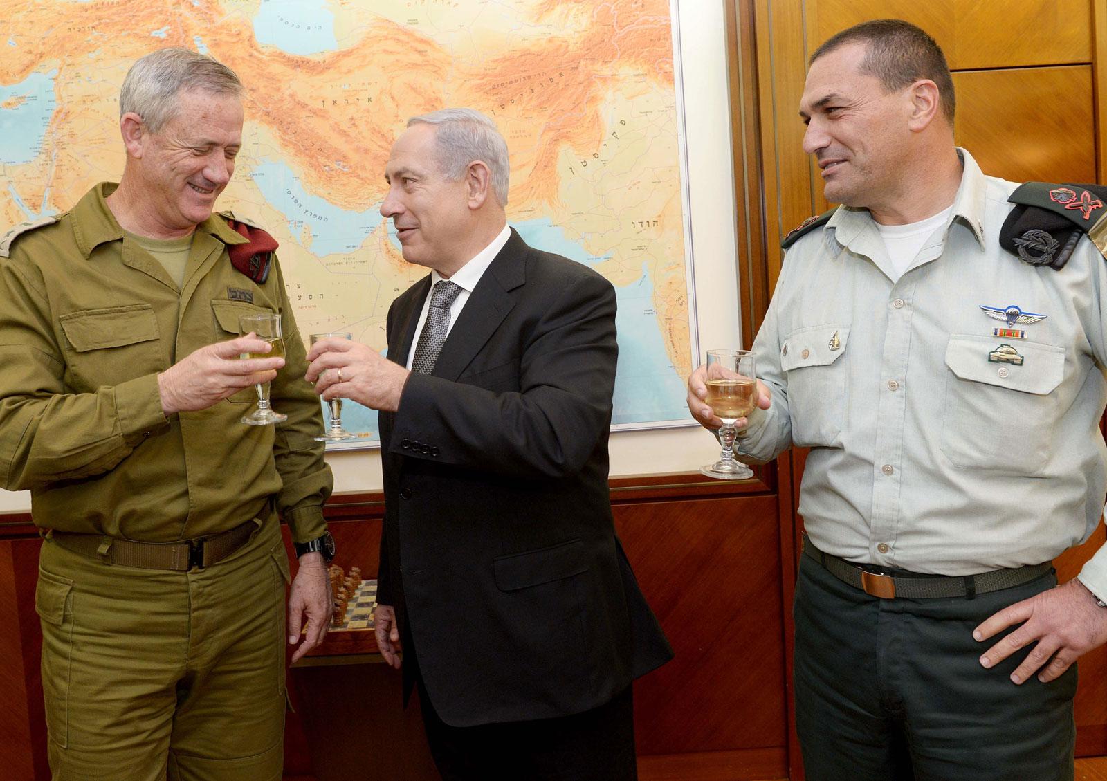 """ראש ממשלת ישראל בנימין נתניהו וראש המטה הכללי בני גנץ משיקים כוסית לכבוד חג הפסח, אתמול (מימין: המזכיר הצבאי איל זמיר. צילום: אבי אוחיון, לע""""מ)"""