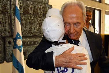 נשיא המדינה שמעון פרס מאמץ אל לבו ילד ששכל את אביו בשירות המדינה, אתמול בבית הנשיא (צילום: אביר סולטן)