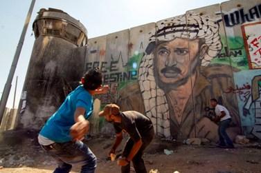 """פלסטינים מיידים אבנים לעבר מגדל שמירה צה""""לי במחסום קלנדיה, לאחר מצעד תמיכה בהכרה באו""""ם במדינה פלסטינית. 17.9.11 (צילום: אורן נחשון)"""