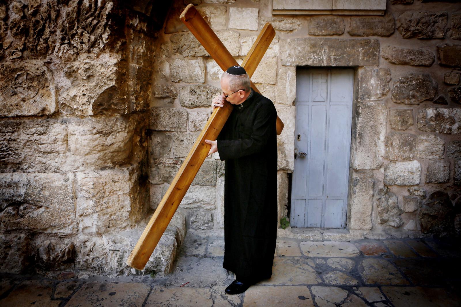 מאמין נוצרי נושא צלב עץ בירושלים, 28.3.13 (צילום: מרים אלסטר)