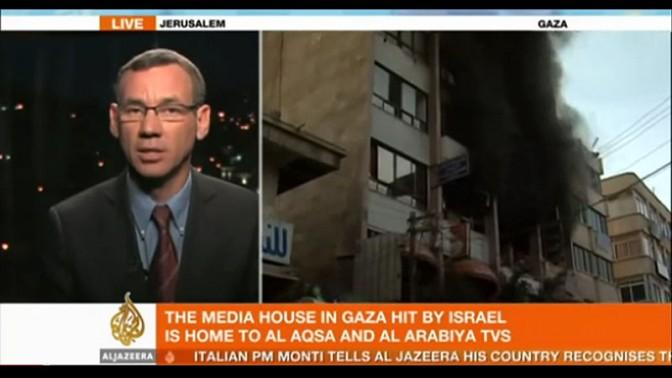 """מארק רגב, יועץ לעיתונות זרה במשרד ראש הממשלה, מתראיין באל-ג'זירה אודות הפצצת בניין טלוויזית אל-אקצא בעזה במסגרת מבצע """"עמוד ענן"""" (צילום מסך)"""