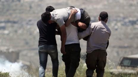 פלסטינים נושאים פצוע בעקבות עימות עם מתנחלים ליד יצהר, אתמול (צילום: עיסאם רימאווי)