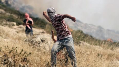 פלסטיני משליך אבן, שלשום ליד רמאללה (צילום: עיסאם רימאווי)