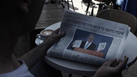אדם קורא ידיעה על איראן, מרץ 2012 (צילום: קובי גדעון)
