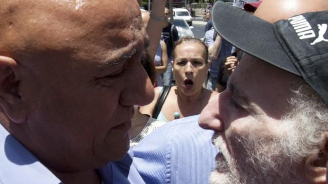 ראש עיריית שדרות, דוד בוסקילה (משמאל) מתעמת עם מפגינים שמוחים על התגייסותו למען נוחי דנקנר (צילום: פלאש 90)