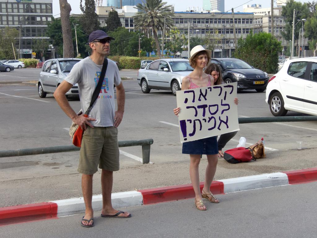 """משמרת מחאה מול אולפני קול-ישראל נגד שיבוץ """"מנחים מאזנים"""" לצידה של קרן נויבך, 26.7.12 (צילום: קפציאל, רשיון cc-by-nc-nd)"""