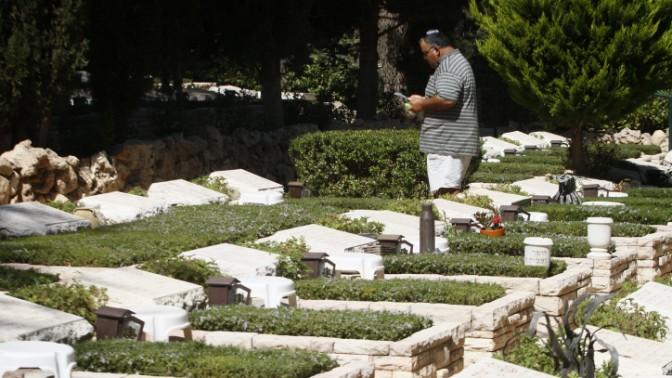 אדם ניצב לצד קברו של חייל שנהרג במלחמת יום-כיפור. בית העלמין הצבאי בהר-הרצל (צילום: אורי לנץ)