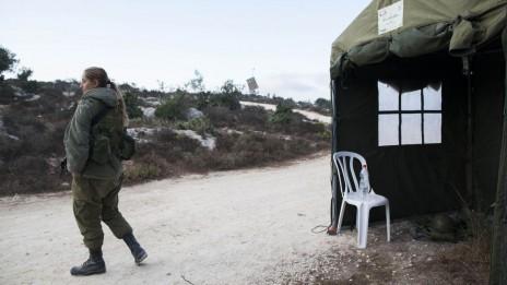 חיילת ישראלית חסרת מעש סמוך לירושלים, אתמול. ברקע: כיפת-ברזל (צילום: יונתן זינדל)