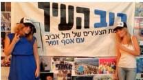 דניאלה סמרי, מגישת החדשות של ערוץ one (מימין), לצד שלט של סיעת רוב-העיר (צילום מסך: דף הפייסבוק של סמרי)