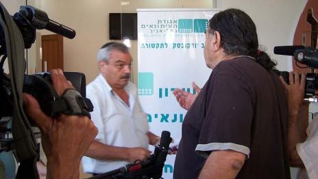 """יוסי בר-מוחא, מנכ""""ל אגודת העיתונאים תל-אביב (משמאל), וכתב הערוץ הראשון נסים מוסק מתעמתים באסיפה הכללית של מועצת העיתונות, 27.6.12 (צילום: """"העין השביעית"""")"""