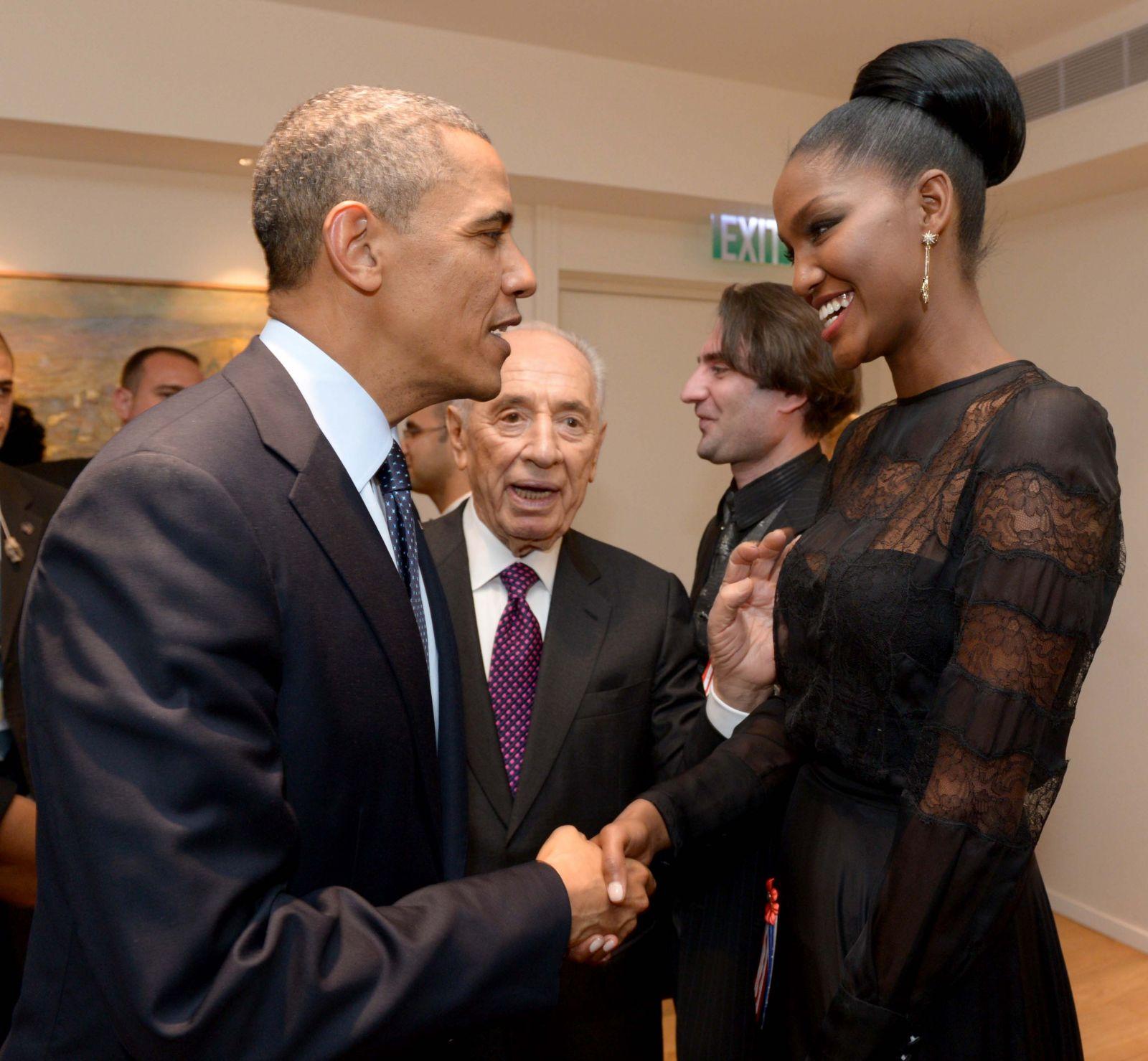 """הדוגמנית ייטאייש (טיטי) איינאו לוחצת את ידו של נשיא ארצות-הברית ברק אובמה בעת ביקורו בישראל. משקיף: הנשיא שמעון פרס (צילום: אבי אוחיון, לע""""מ)"""
