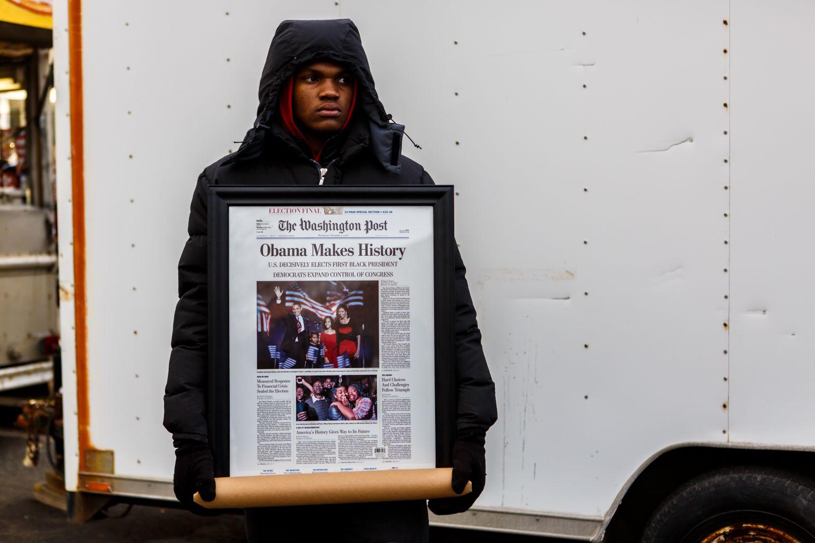 """מוכר עיתונים אמריקאי אוחז שער ממוסגר של ה""""וושינגטון פוסט"""", 21.1.13 (צילום: Chris Parypa Photography / Shutterstock)"""