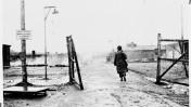 חייל אמריקאי צועד דרך שער מחנה העבודה קאופרינג 1 (לנדסברג) המסונף למחנה הריכוז דכאו ביום שחרור המחנה, 27.4.1945 (צילום: National Archives and Records Administration, College Park, נחלת הכלל)